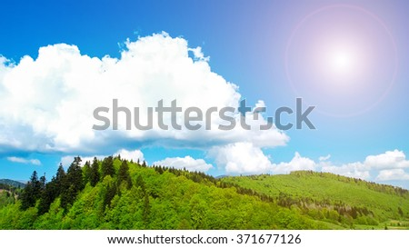 big white cloud over the mountains covered with the green wood in sun beams.  mountain woods, the blue sky and clouds in the Carpathians, Ukraine. The sun lighting with mountain beams, trees, clouds. - stock photo