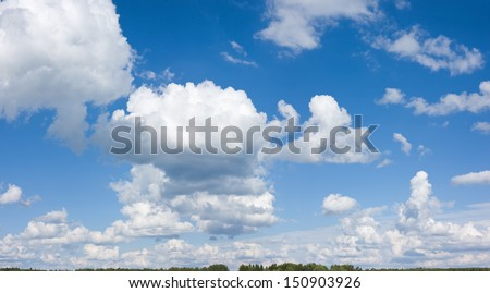 Big white cloud under the sunlight on the blue sky over the thin line of forest - stock photo
