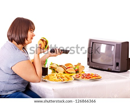 Big woman eating fast food and watching TV. Isolated. - stock photo
