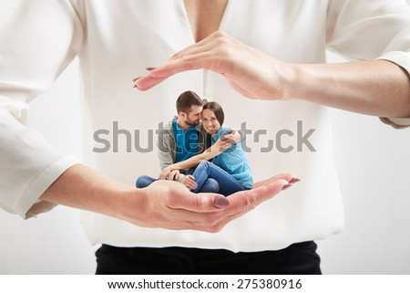 big woman's hands holding small couple and covering them - stock photo
