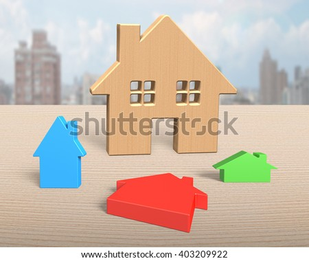 Big wooden house with three colorful small houses on table, with city skyscraper background. - stock photo