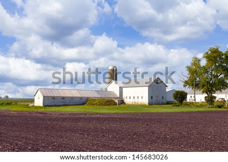 Big wooden white farm and barn in the summer with moody sky  - stock photo
