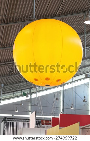 Big yellow advertising balloon in exhibition hall - stock photo