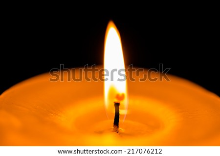 Big yellow candle and flame on dark background  - stock photo