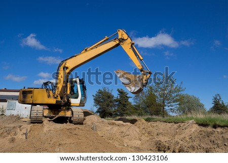 big yellow excavators working on a construction site - stock photo