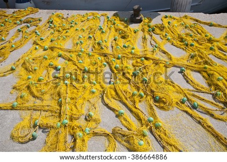 big yellow fishing net with floats closeup on pier - stock photo