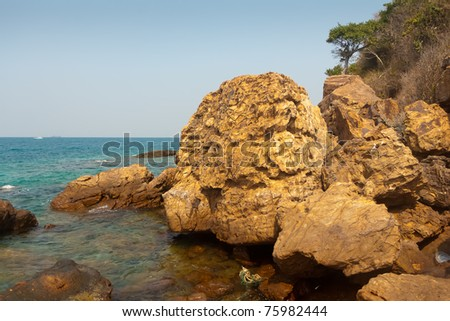 Big yellow stones on the shore of an exotic island