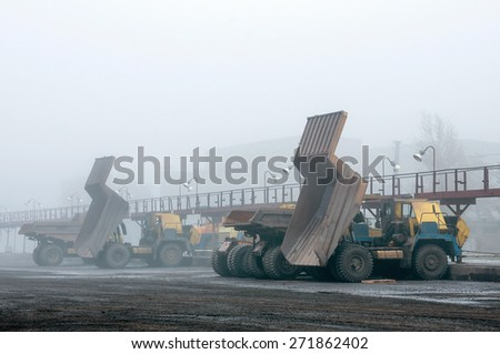 big yellow trucks at technical services area in fog - stock photo