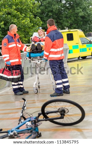 Bike accident paramedics with woman on emergency stretcher ambulance aid