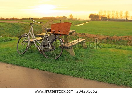 Bike against a picnic bench in the countryside from the Netherlands at twilight - stock photo