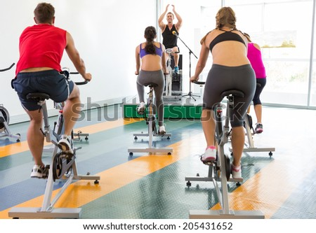 Bike class working out with motivational instructor at the gym - stock photo