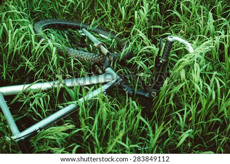 bike cross country lies in the green grass, cycling and active kind of holiday - stock photo