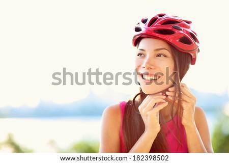 Bike helmet - woman putting biking helmet on outside during bicycle ride. - stock photo