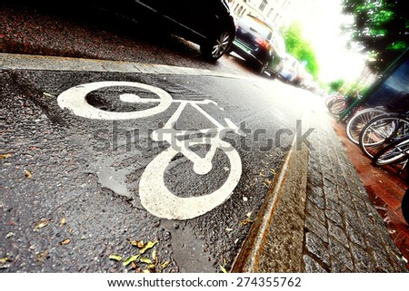 Bike lane and car queue after the rain into the bright light - stock photo