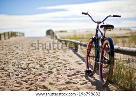 Bike left on sandy beach trail - stock photo