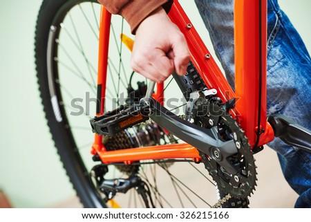 Bike maintenance: mechanic serviceman repairman installing assembling or adjusting bicycle gear on wheel in workshop - stock photo