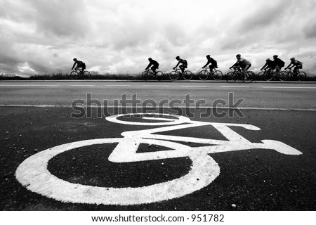bike race in denmark, cyclist are passing by a bike sign on the road. Shot with low shutter speed to achieve motion blur - stock photo
