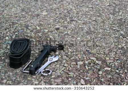 Bike repair tools on asphalt - stock photo