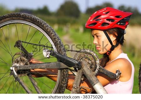 Bike repair. Woman repairing mountain bike. - stock photo