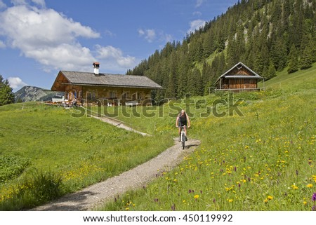 Bike ride of a cyclist to Enningalm in the Ammergau Alps - stock photo