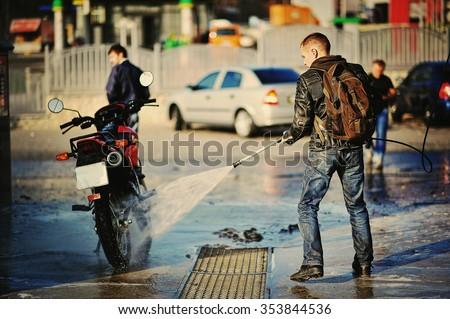 Bike rider washing his motorcycle - stock photo