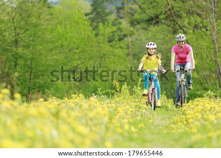 Bike riding - young girl with mother on bike, active family concept - stock photo