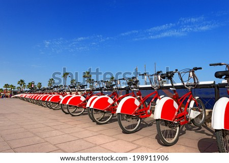 Bike Sharing in Barcelona Spain / Long row of red and white bicycles (public bikes) near the harbor in Ronda Litoral, Barcelona - Spain - stock photo
