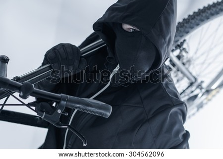 Bike Theft. Bike Thief in a Hood, Black Mask and Black Gloves. Caucasian Male Thief. - stock photo