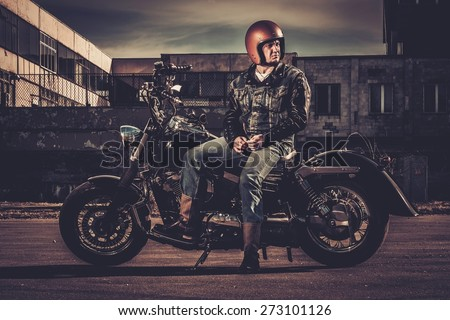 Biker and his bobber style motorcycle on a city streets  - stock photo