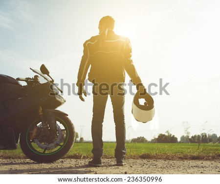 biker and motorcycle in the countryside. concept about people and transportation - stock photo