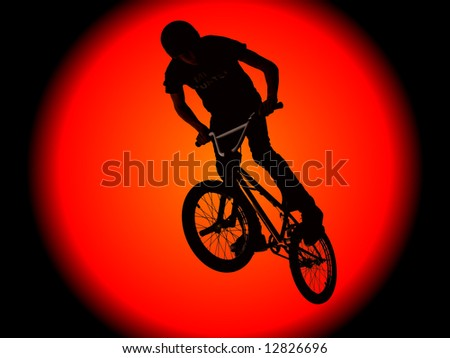 Biker boy silhouetted against a huge sun