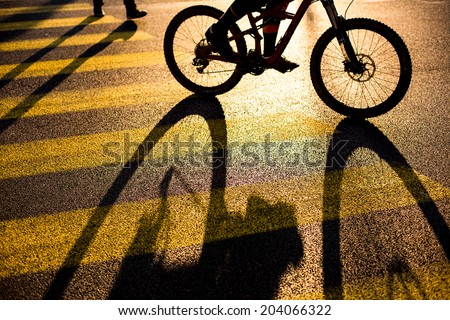 Biker/Cyclist on a crossing in a city casting a long shadow - stock photo