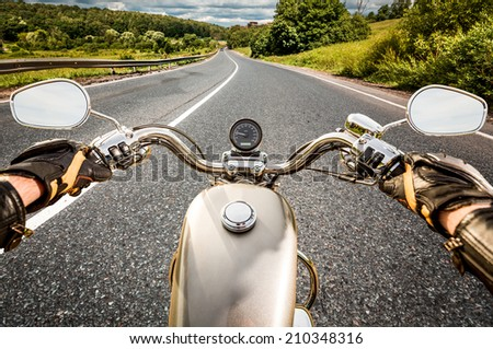 Biker driving a motorcycle rides along the asphalt road. First-person view. - stock photo