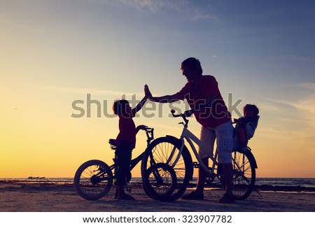 Biker family silhouette, father with two kids on bikes at sunset - stock photo