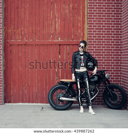 Biker girl and vintage custom motorcycle. Outdoor lifestyle portrait
