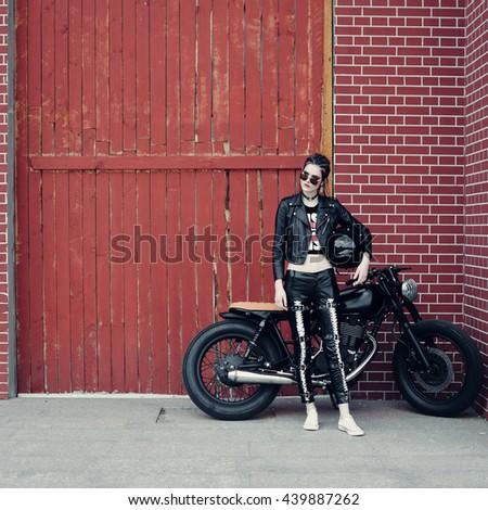 Biker girl and vintage custom motorcycle. Outdoor lifestyle portrait - stock photo