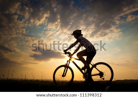 Biker-girl at the sunset on the meadow - stock photo