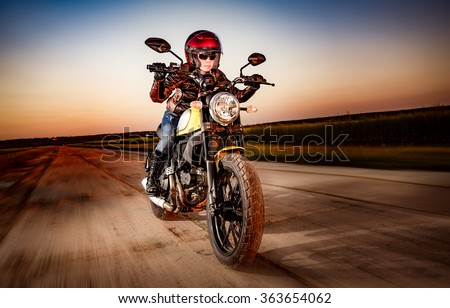 Biker girl in a leather jacket and helmet on a motorcycle - stock photo