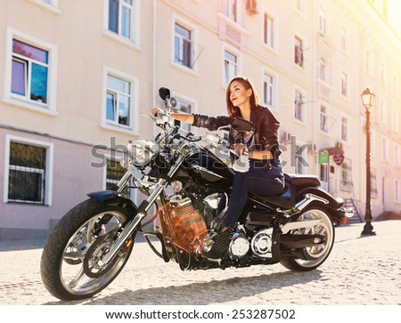 Biker girl in a leather jacket riding a motorcycle with ligth leak and motion effect - stock photo