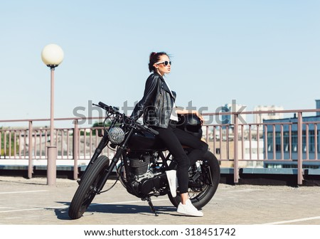 Biker girl in leather jacket sitting on vintage custom motorcycle. Outdoor lifestyle portrait - stock photo