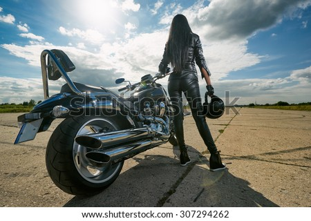 Biker girl in leather jacket standing by a motorcycle. Rear view - stock photo