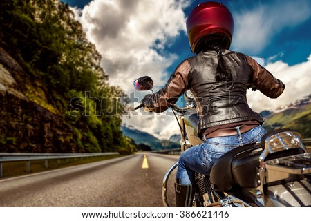 Biker girl rides a motorcycle in the rain. First-person view. - stock photo