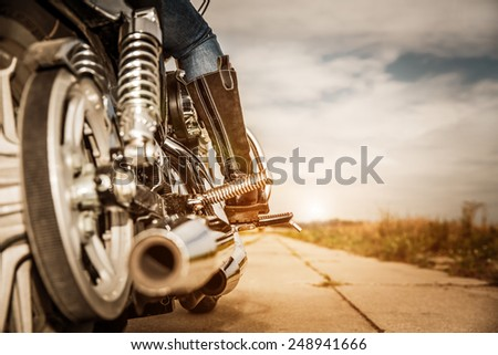 Biker girl riding on a motorcycle. Bottom view of the legs in leather boots. - stock photo