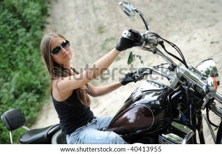 Biker girl sitting on her bike - stock photo