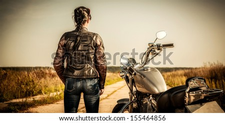 Biker girl stands on the road and looks into the distance - stock photo