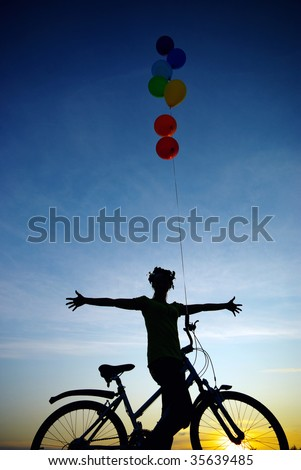 Biker girl with balloons. Silhouette in sunset.