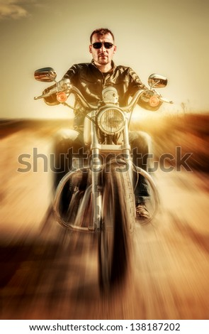 Biker in a leather jacket riding a motorcycle on the road - stock photo