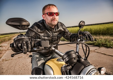 Biker in a leather jacket riding a motorcycle on the road. Filter applied in post-production. - stock photo