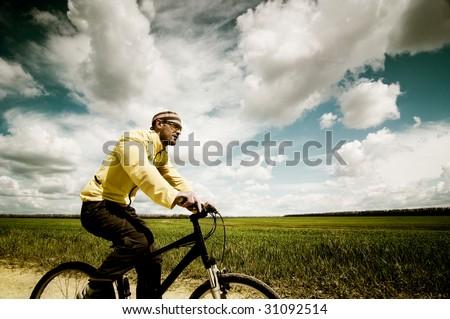 biker in green summer field - stock photo