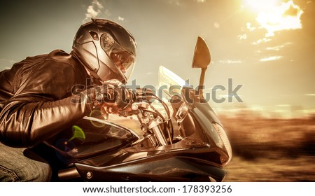 Biker in helmet and leather jacket racing on the road. Filter applied in post-production. - stock photo
